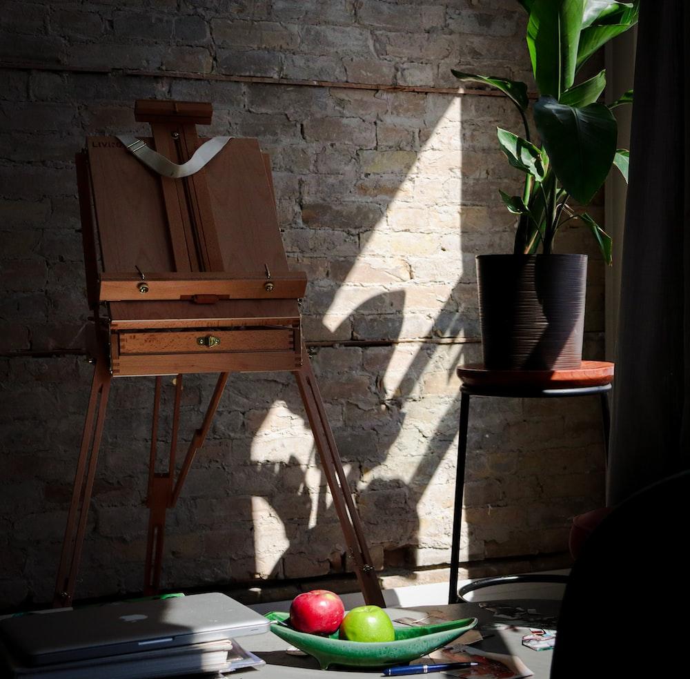 brown wooden chair beside green apple fruit