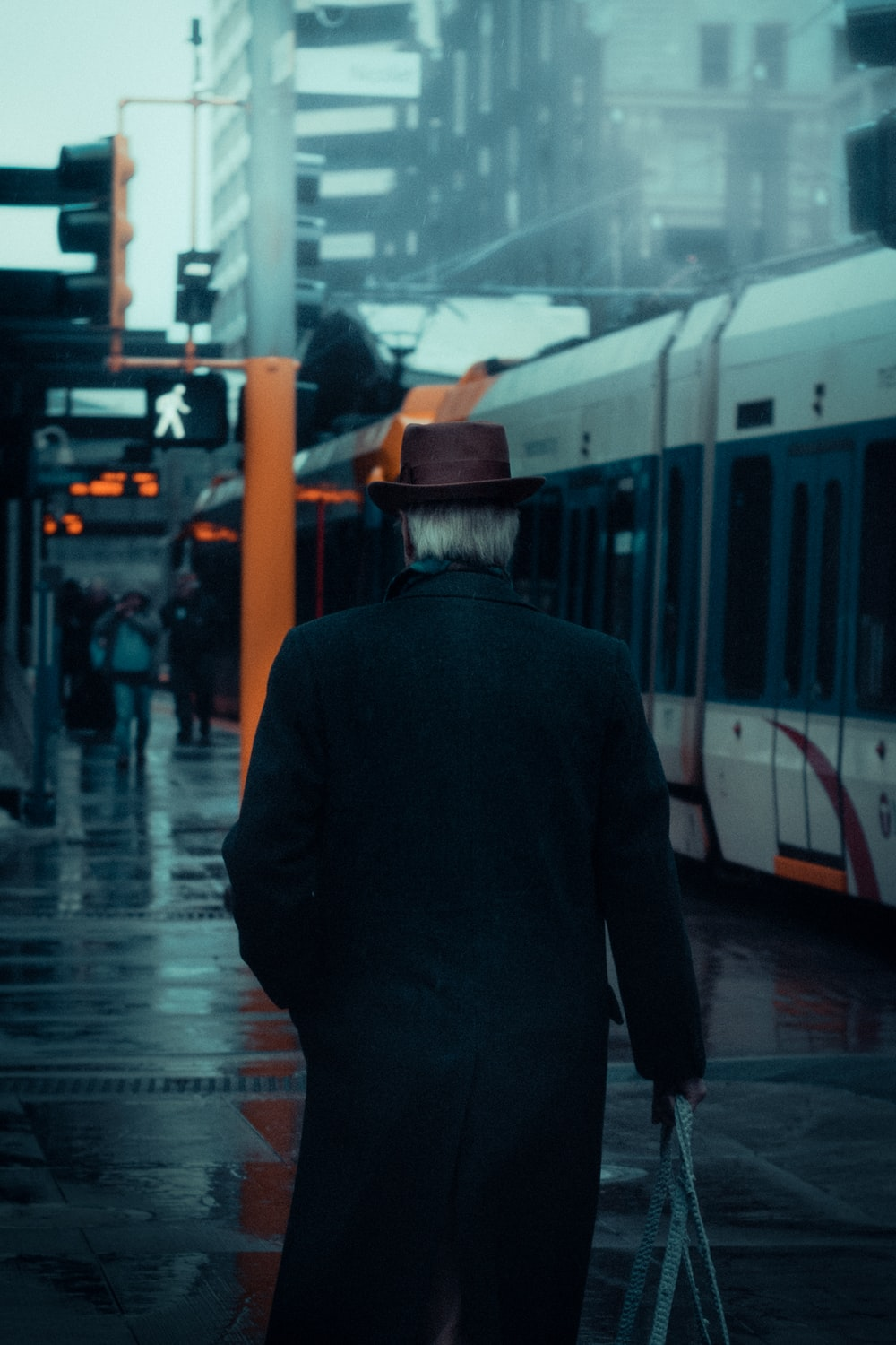 man in black jacket and brown hat standing in front of white train