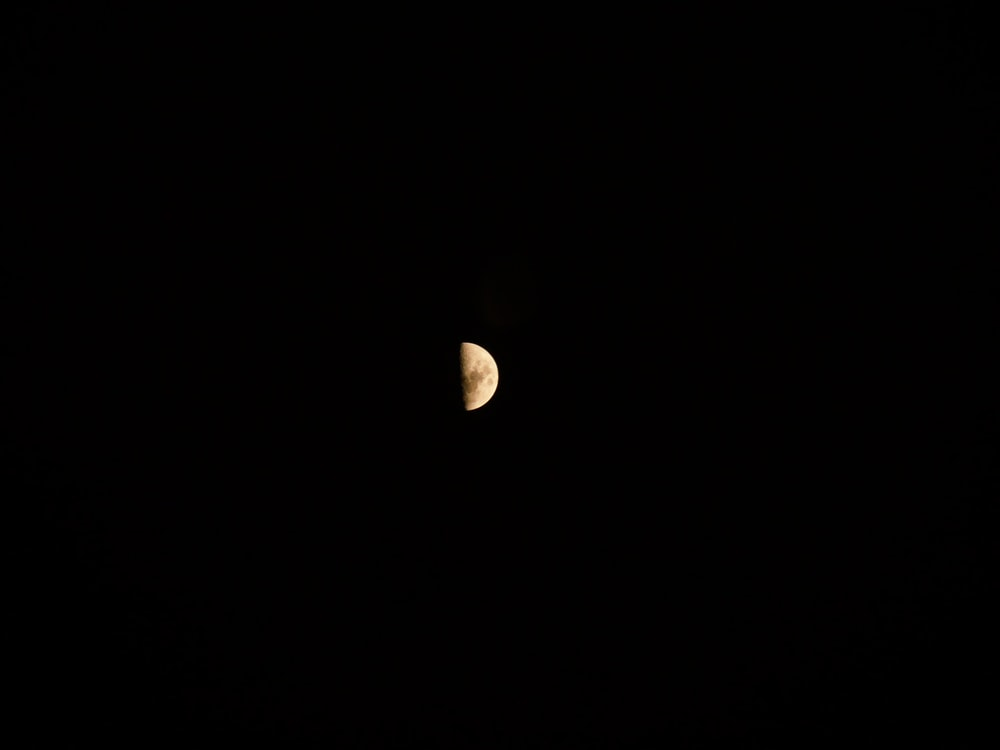 white half moon in dark night sky