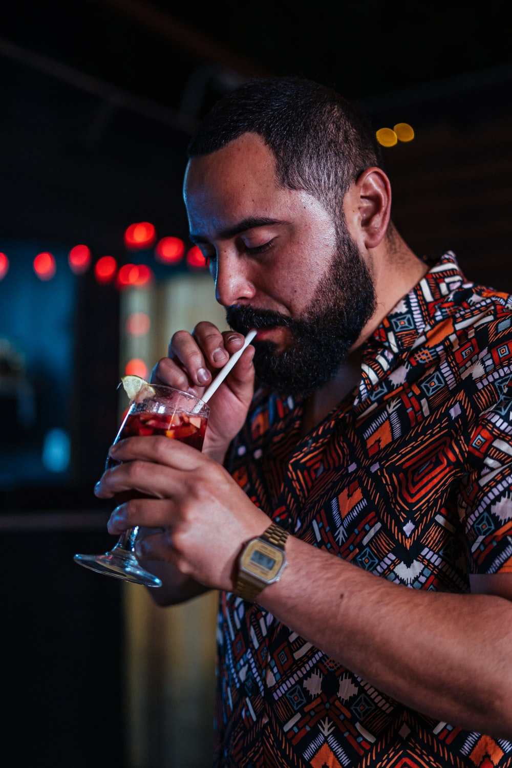 man in red and black plaid button up shirt drinking from clear drinking glass