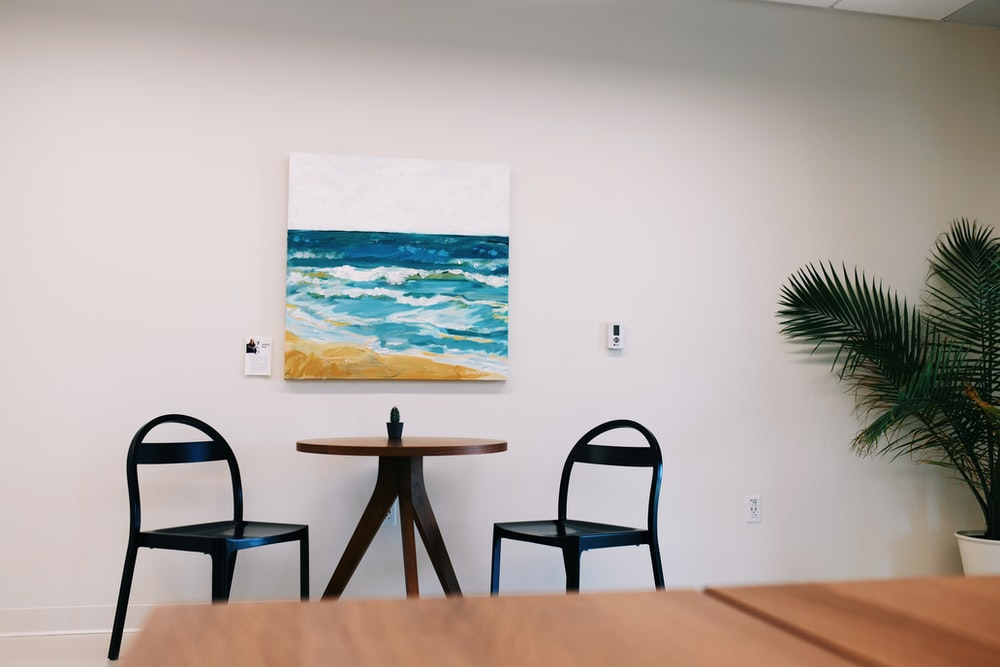 black wooden table and chairs near sea painting