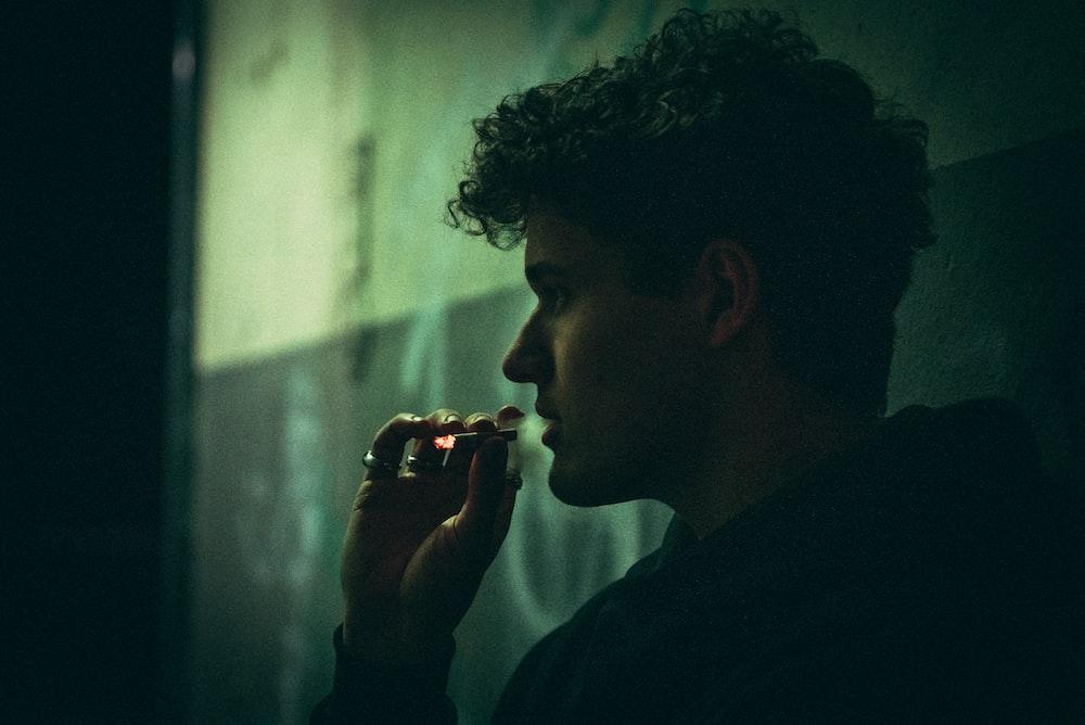 man in black shirt smoking cigarette
