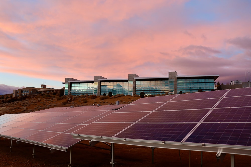 solar panels on brown field under white clouds during daytime