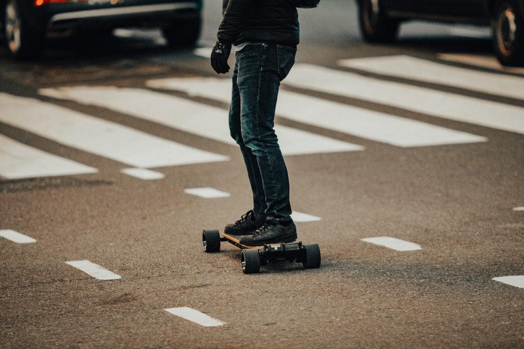 Person In Black Jacket and Blue Denim Jeans Walking On Pedestrian Lane During Daytime - unsplash