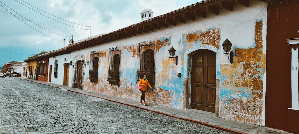 woman in blue dress walking on street during daytime