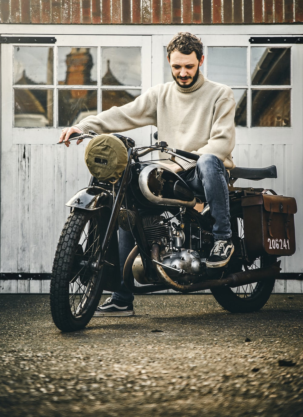 man in gray hoodie riding black and brown cruiser motorcycle