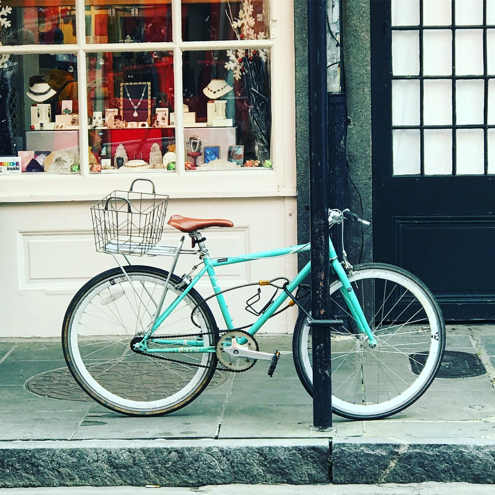 teal city bike parked beside store
