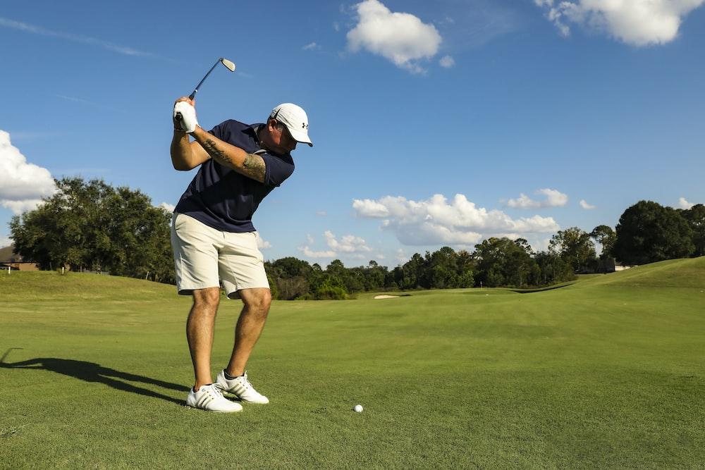 man in black shirt and white shorts playing golf during daytime
