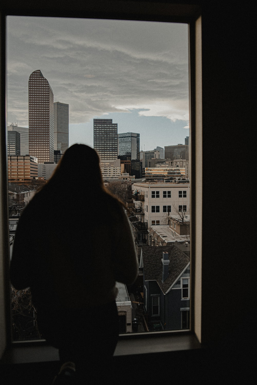 woman in black jacket standing on top of building during daytime