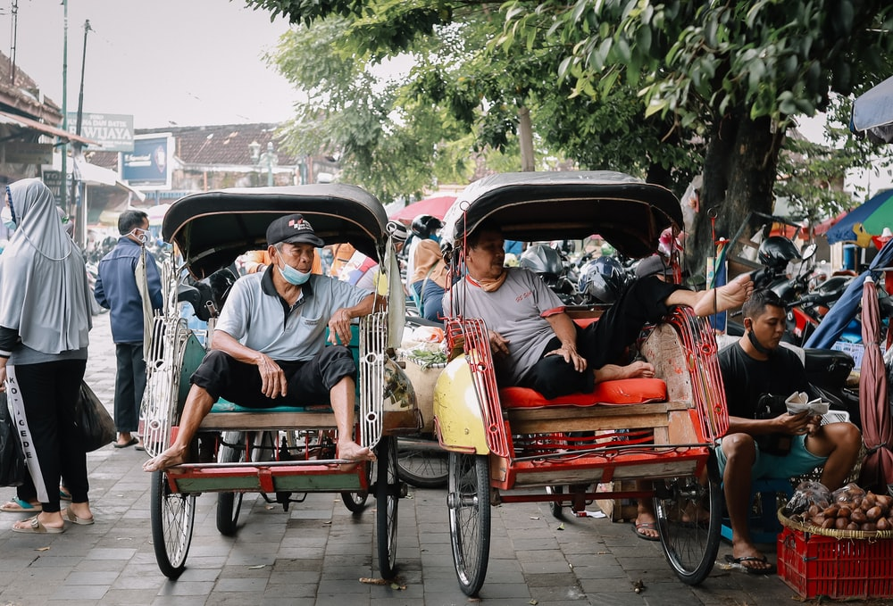 people riding on red and black auto rickshaw during daytime