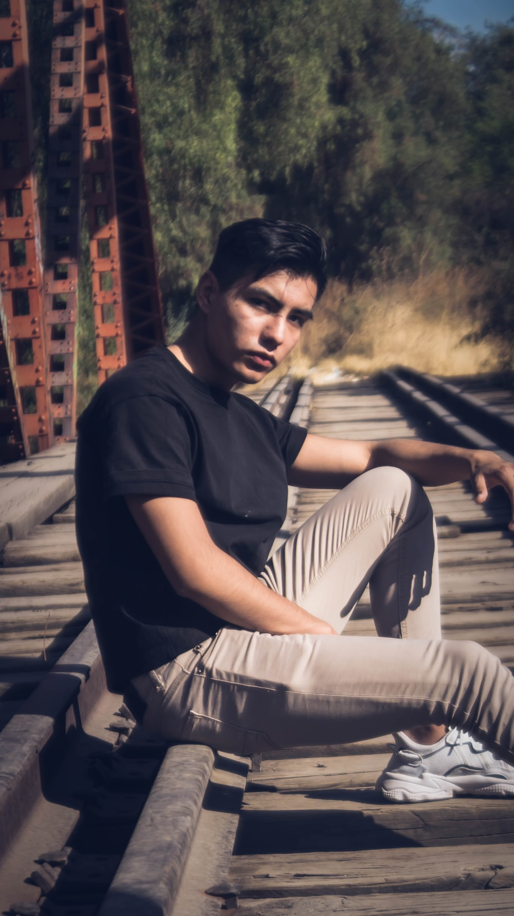 man in black crew neck t-shirt and white pants sitting on brown wooden bench