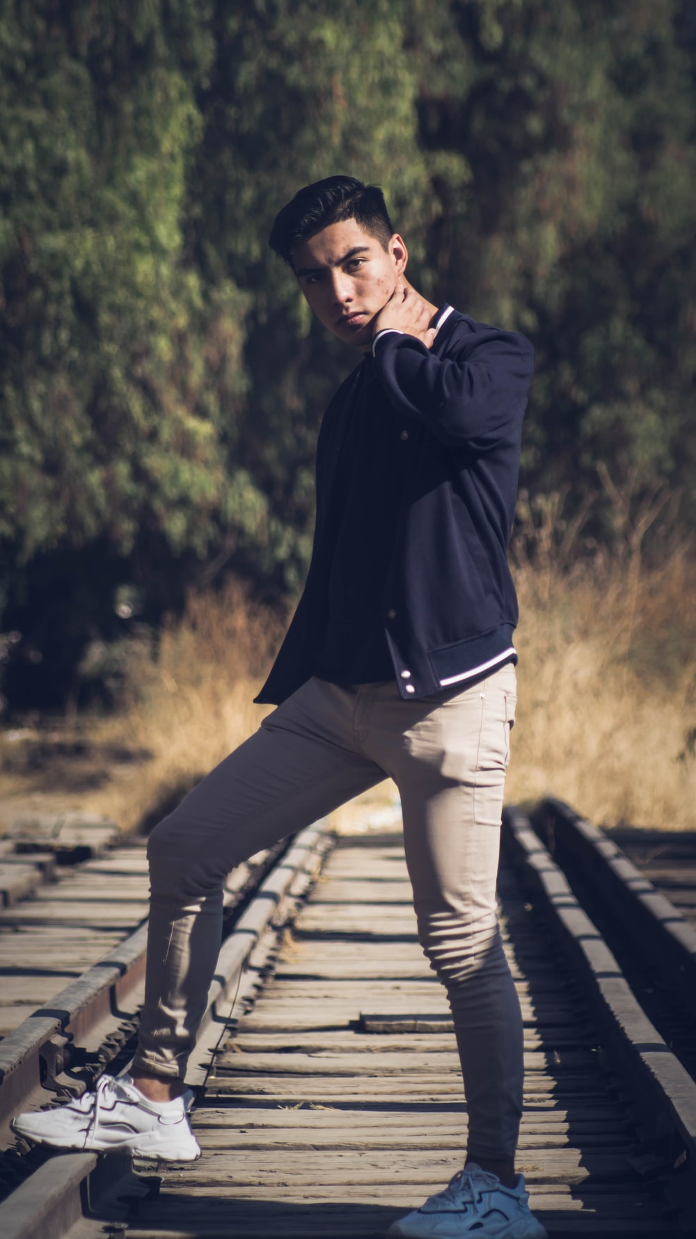 man in black jacket and white pants standing on wooden pathway during daytime