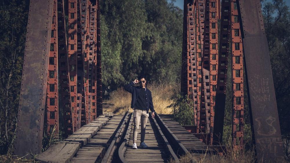 man in black jacket walking on train rail during daytime