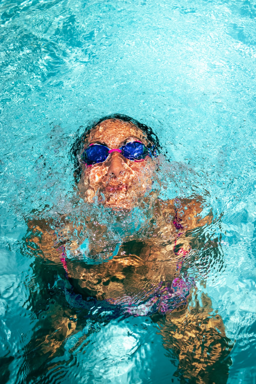 woman in green and black floral bikini top wearing blue sunglasses