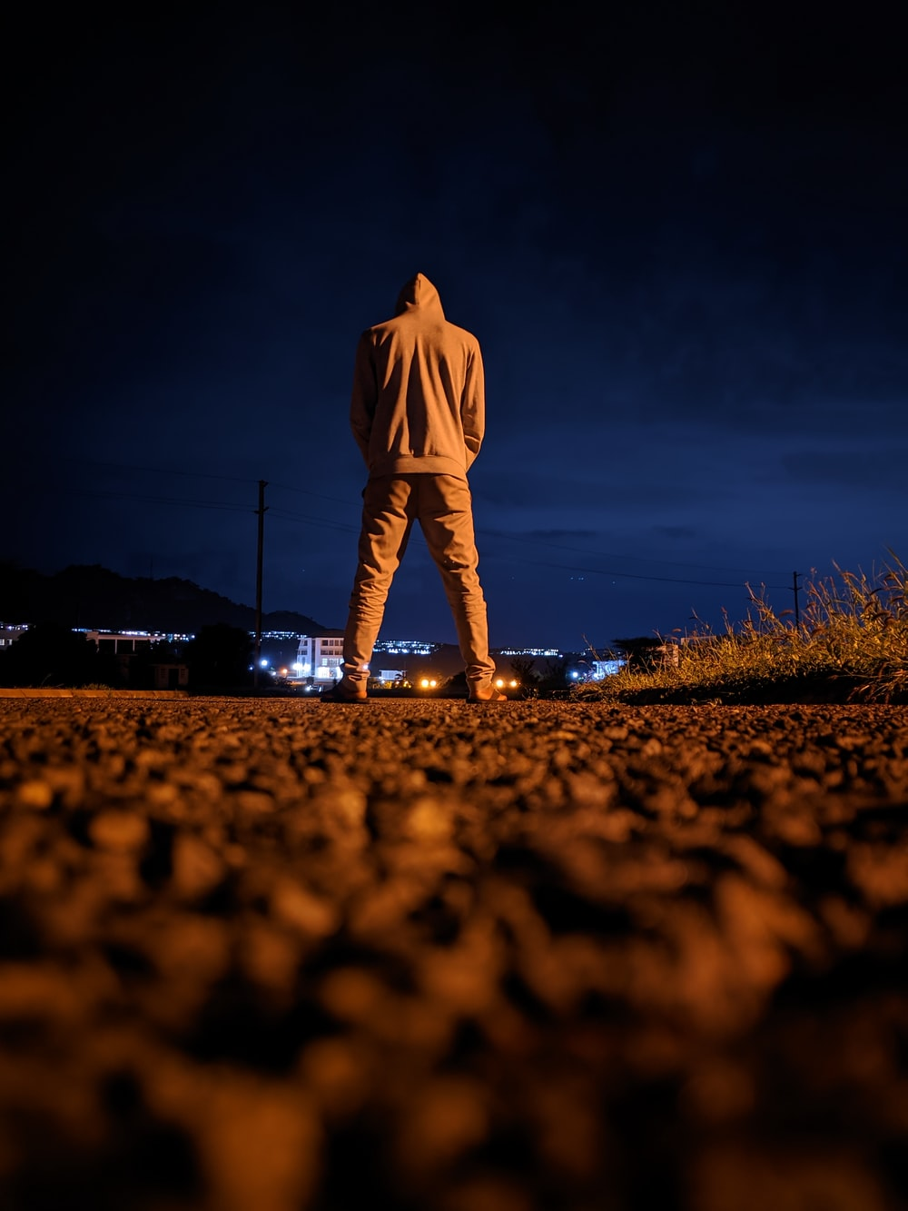 man in white long sleeve shirt and pants standing on brown field during night time