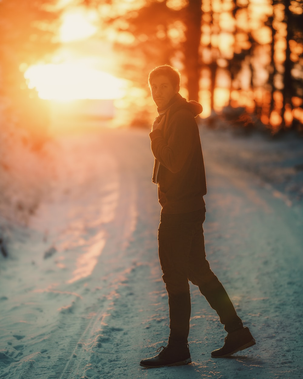 man in brown jacket standing on snow covered ground during daytime