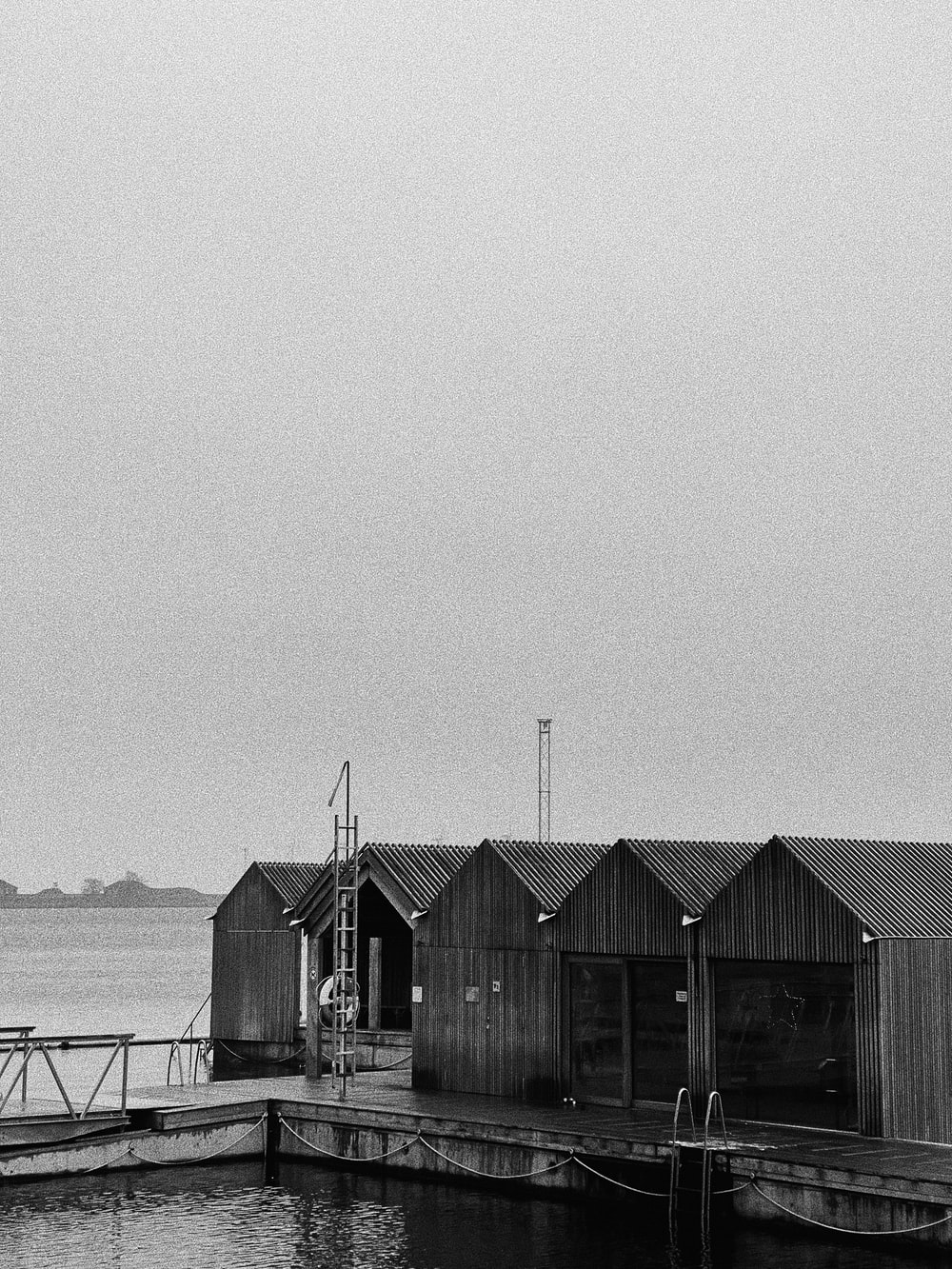 grayscale photo of wooden house on sea