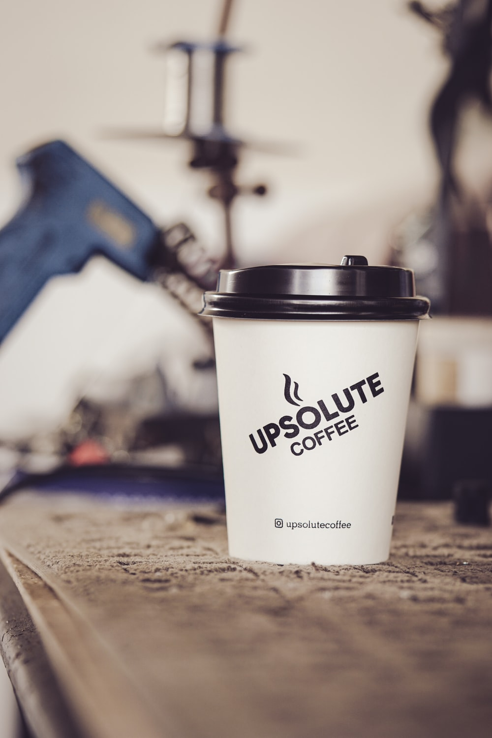 white and black disposable cup on brown wooden table