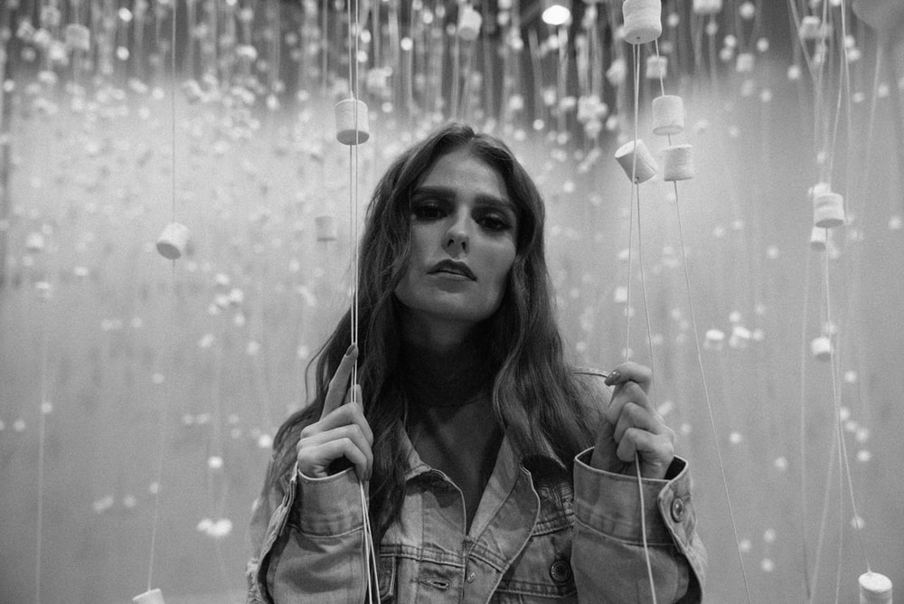 grayscale photo of woman in plaid shirt holding string lights