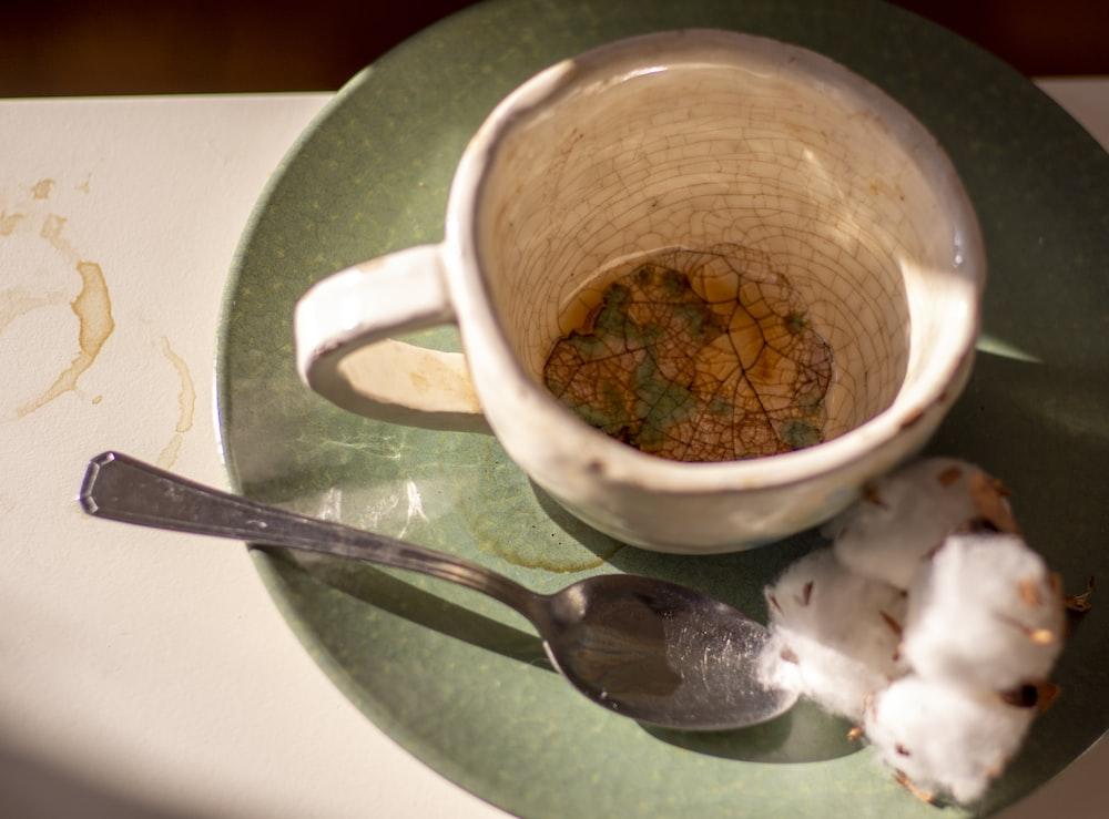 white ceramic mug beside stainless steel spoon