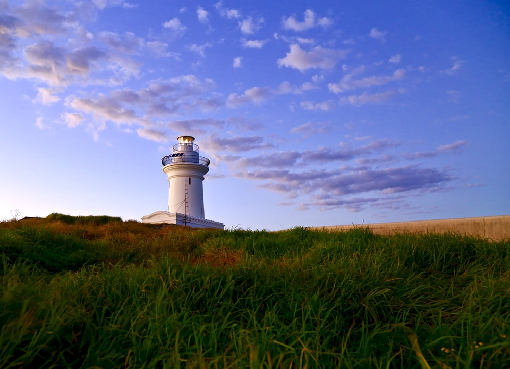 white lighthouse under blue sky and white clouds during daytime