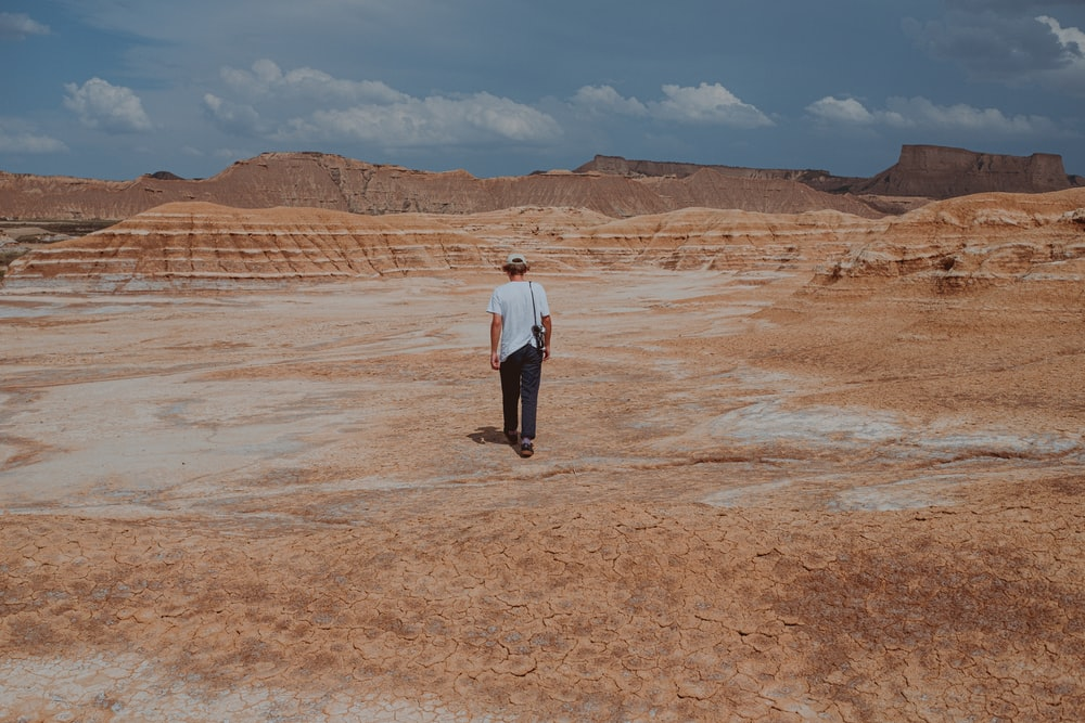 man in white dress shirt and black pants standing on brown sand during daytime