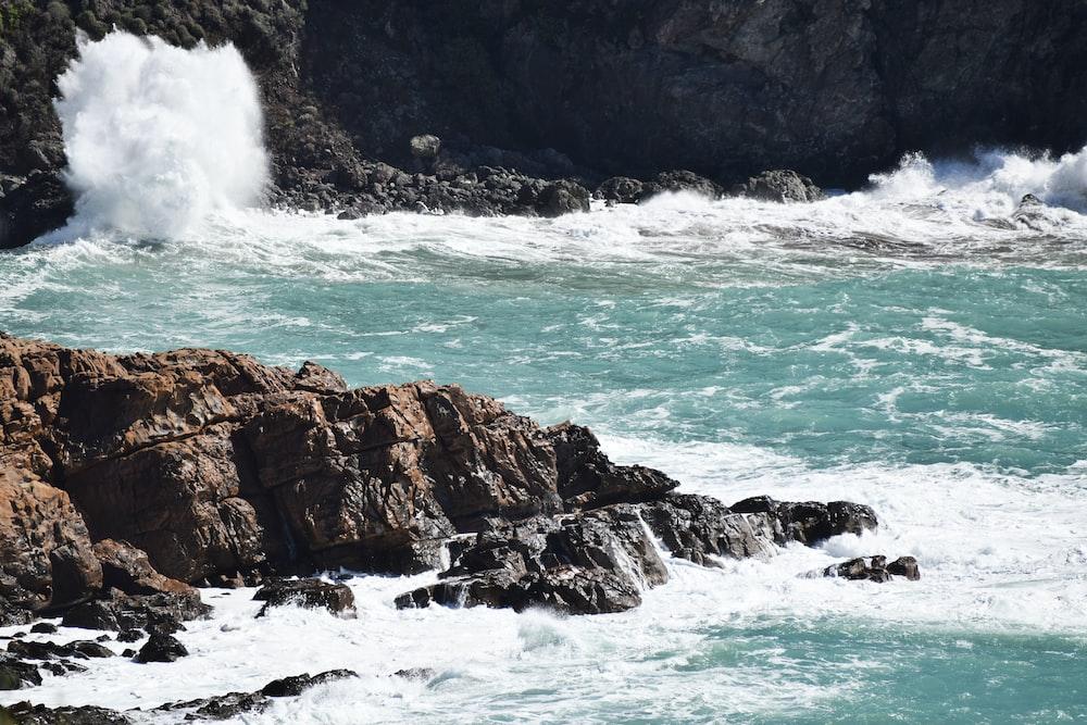 water waves hitting brown rocky shore during daytime