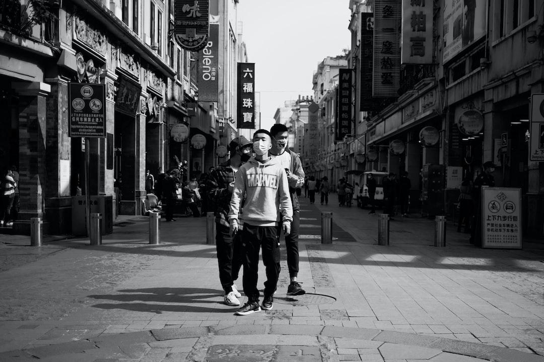Man In White Long Sleeve Shirt Walking On Sidewalk In Grayscale Photography - unsplash