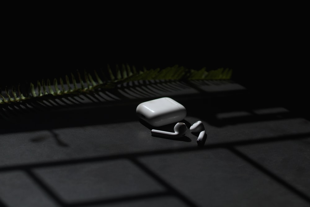 white apple airpods on black surface