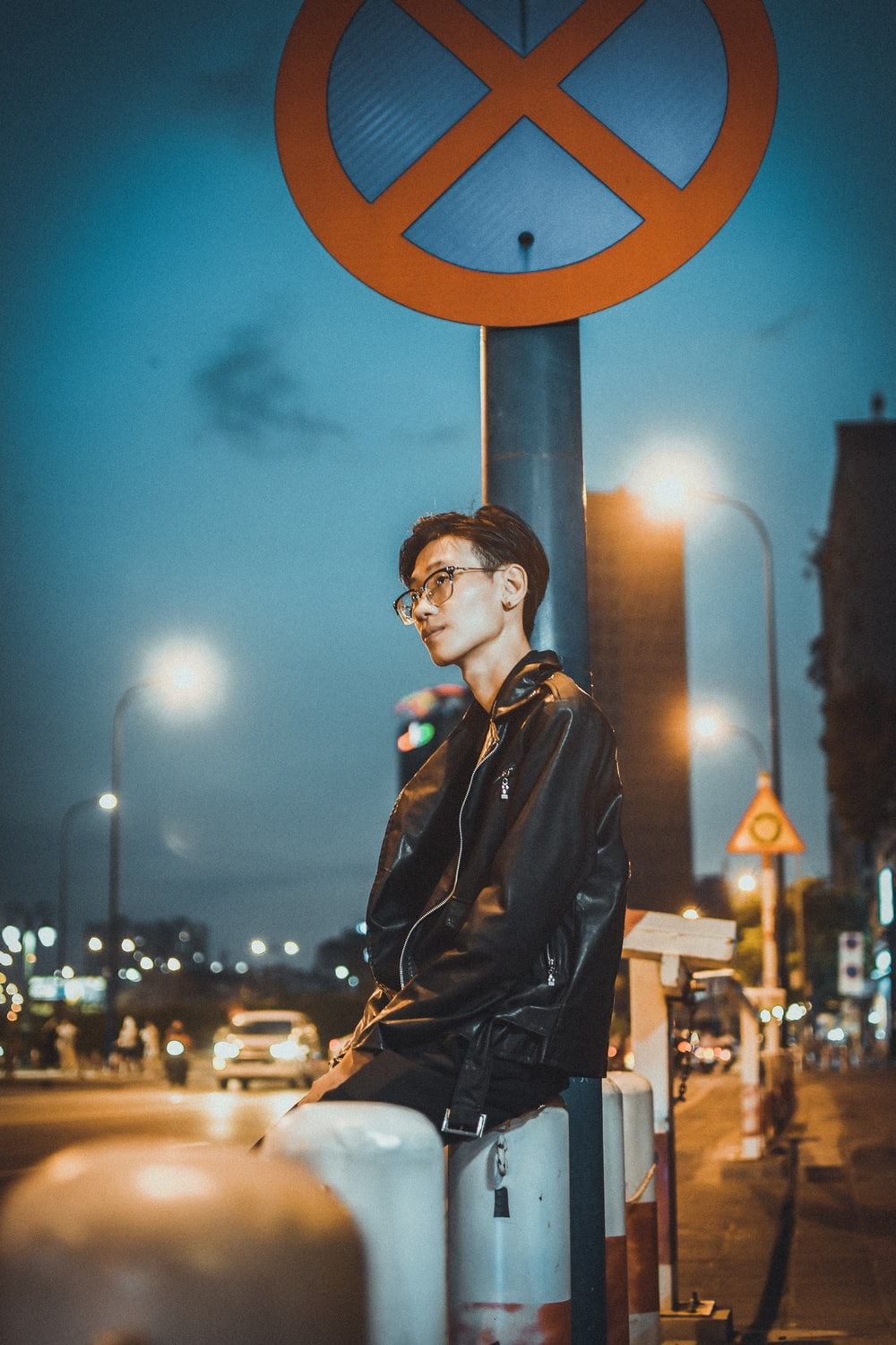 man in black leather jacket standing near brown round metal stand during night time