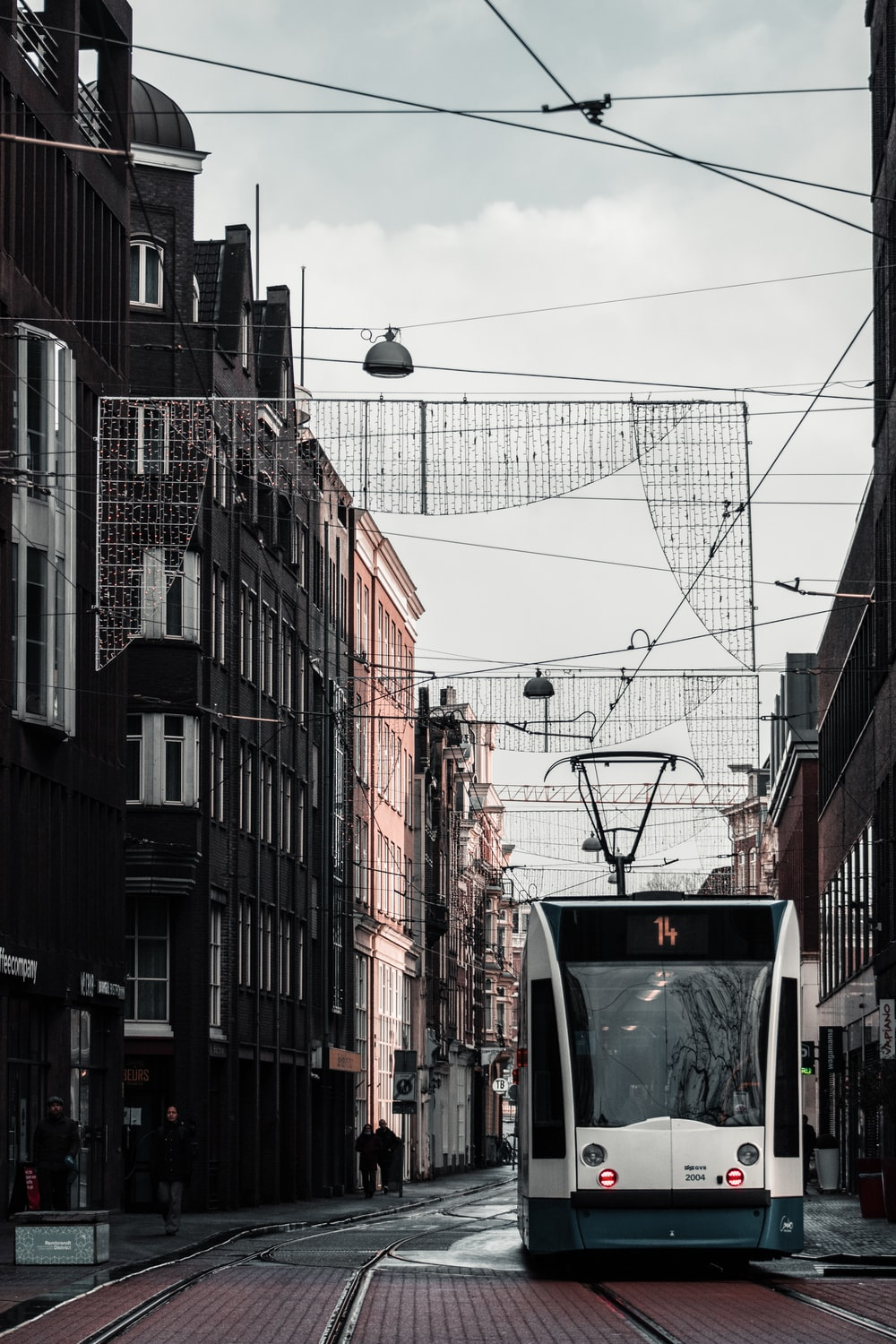 white and black cable car in between of buildings during daytime