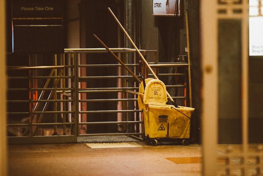 yellow plastic trash bin beside black metal stair railings