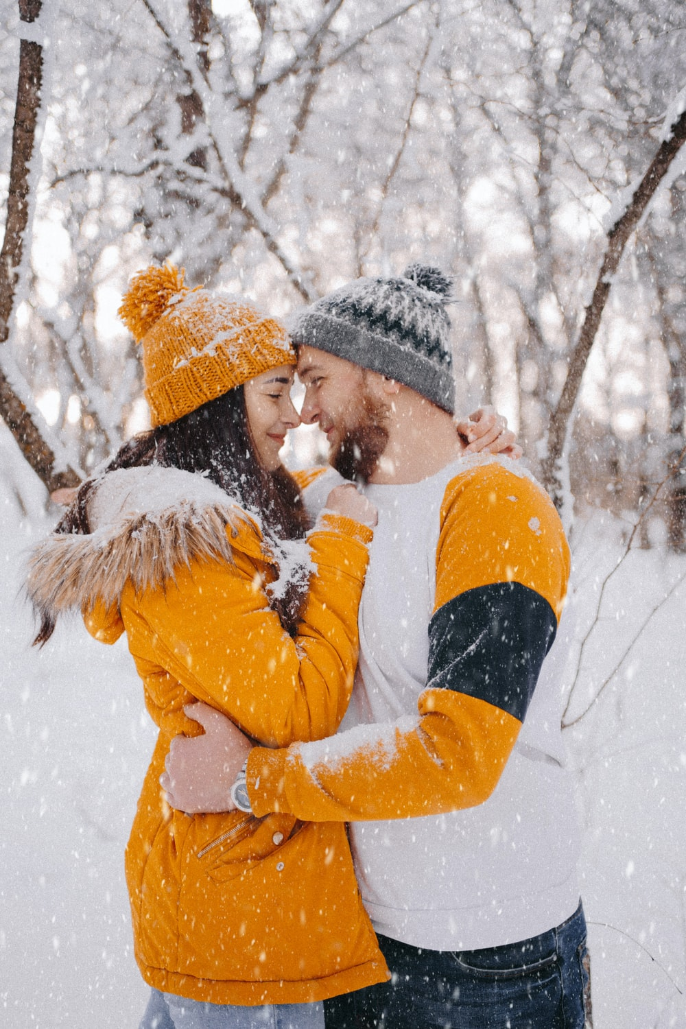 woman in yellow jacket and black knit cap kissing man in black jacket