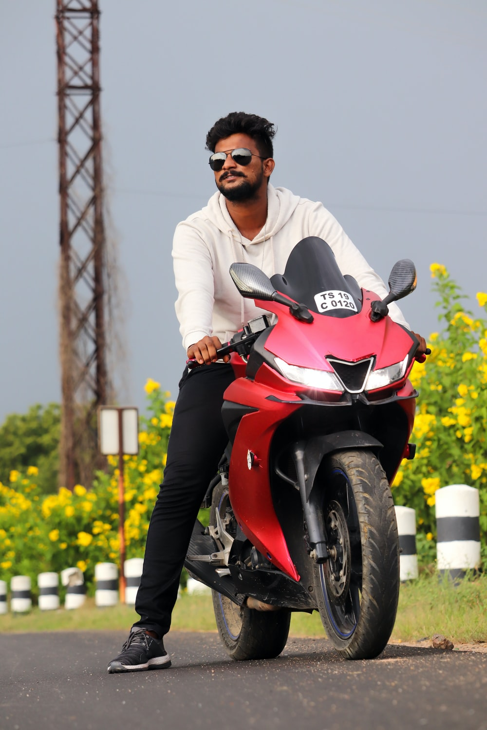 man in white dress shirt riding red and black motorcycle