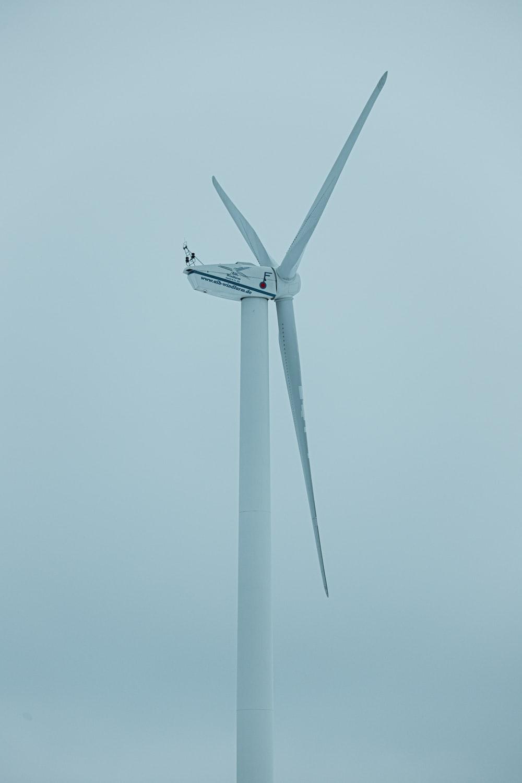 white wind turbine under blue sky