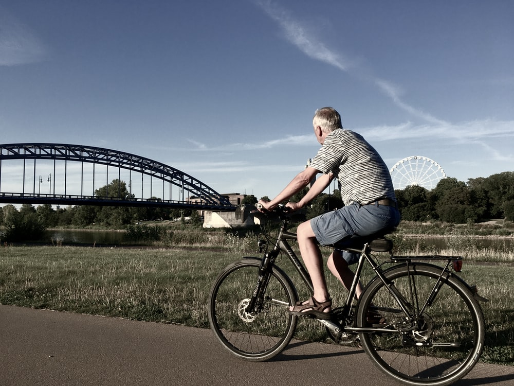 man in gray and white striped shirt riding black bicycle on road during daytime