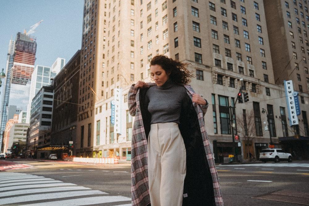 woman in black coat standing on pedestrian lane during daytime