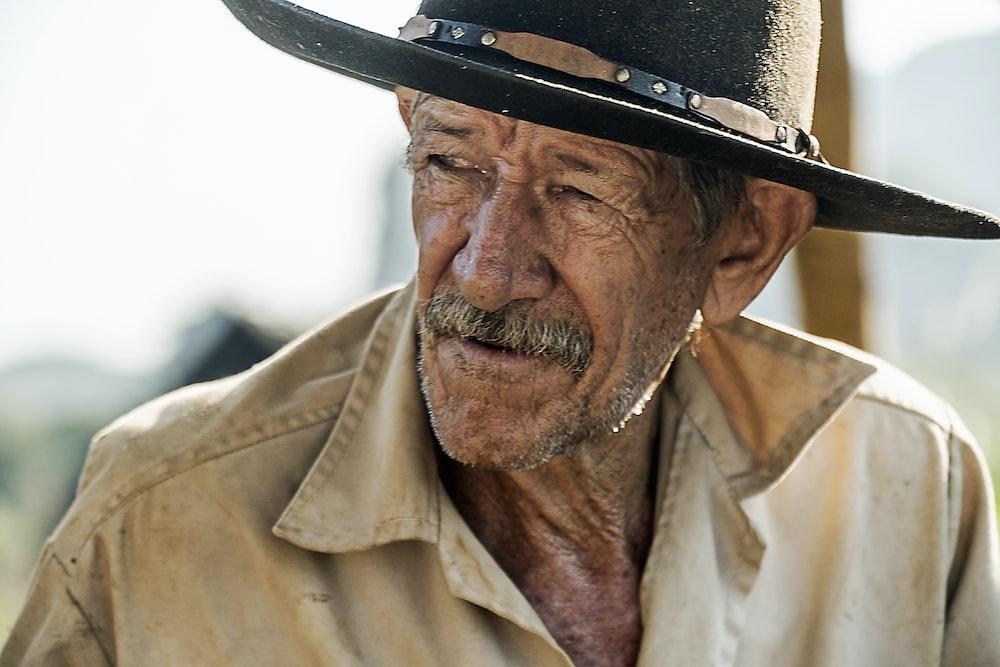 man in beige button up shirt wearing black fedora hat