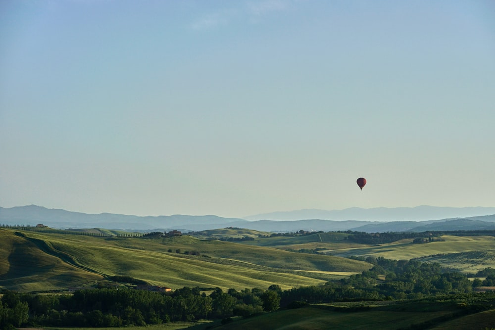red hot air balloon flying over green grass field during daytime