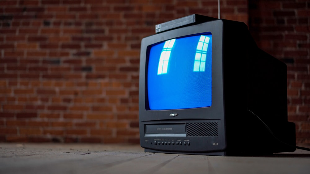gray crt tv turned on beside brown brick wall