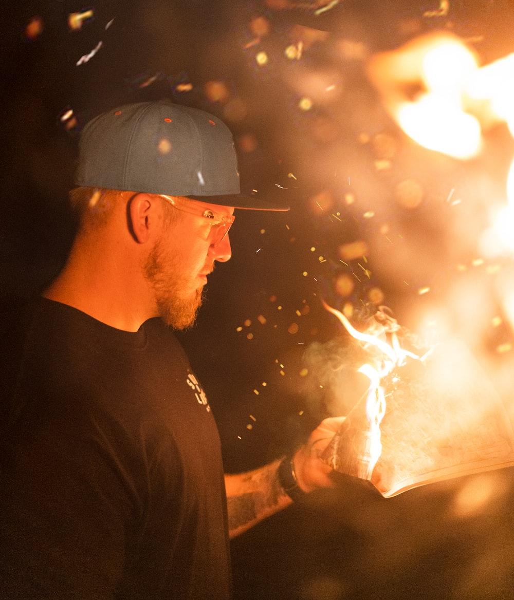 man in black crew neck shirt holding fire