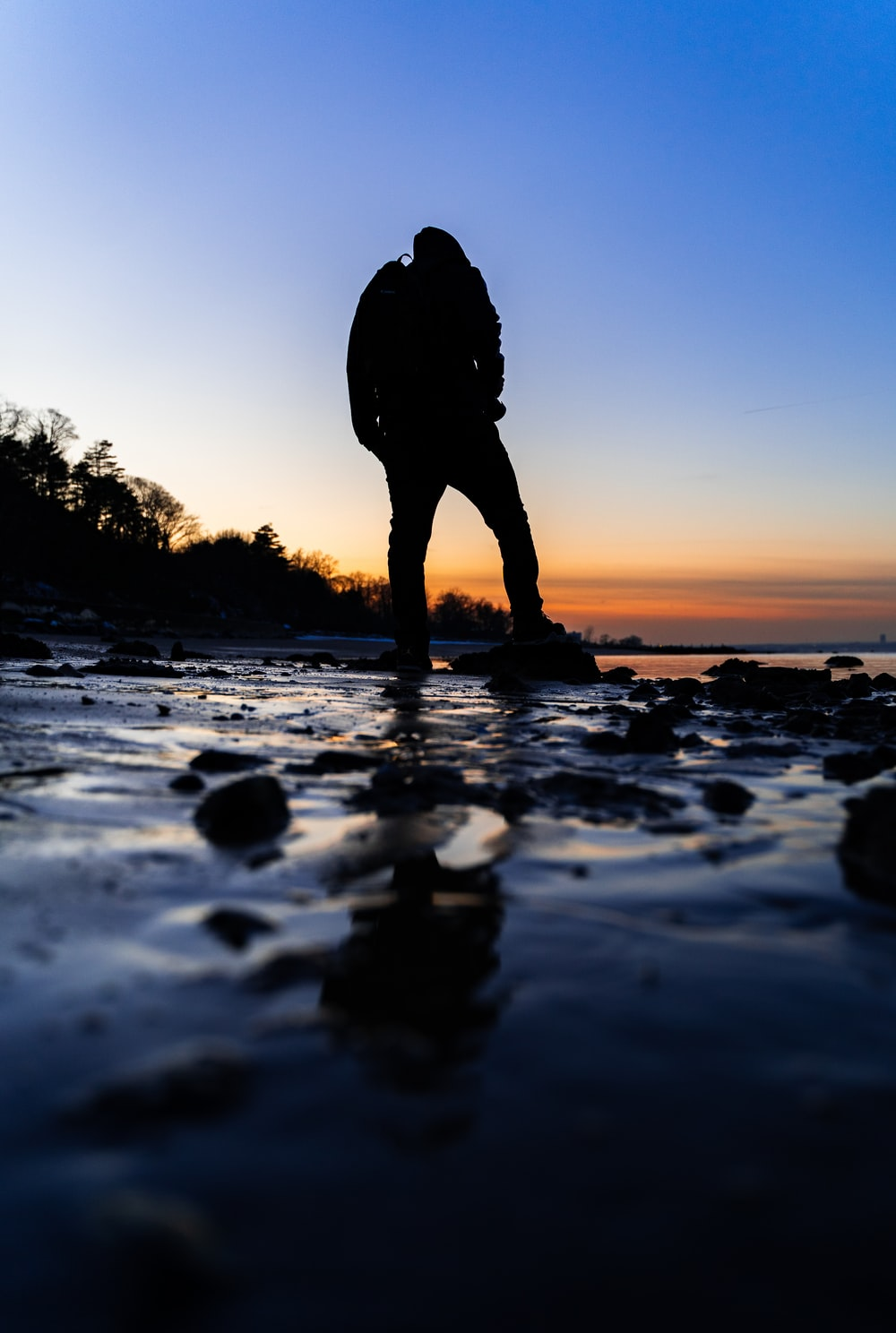 silhouette of person standing on rocky shore during sunset