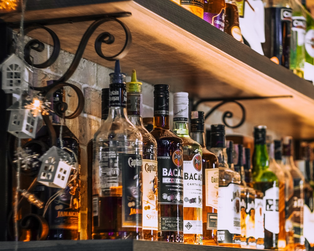 assorted glass bottles on brown wooden shelf