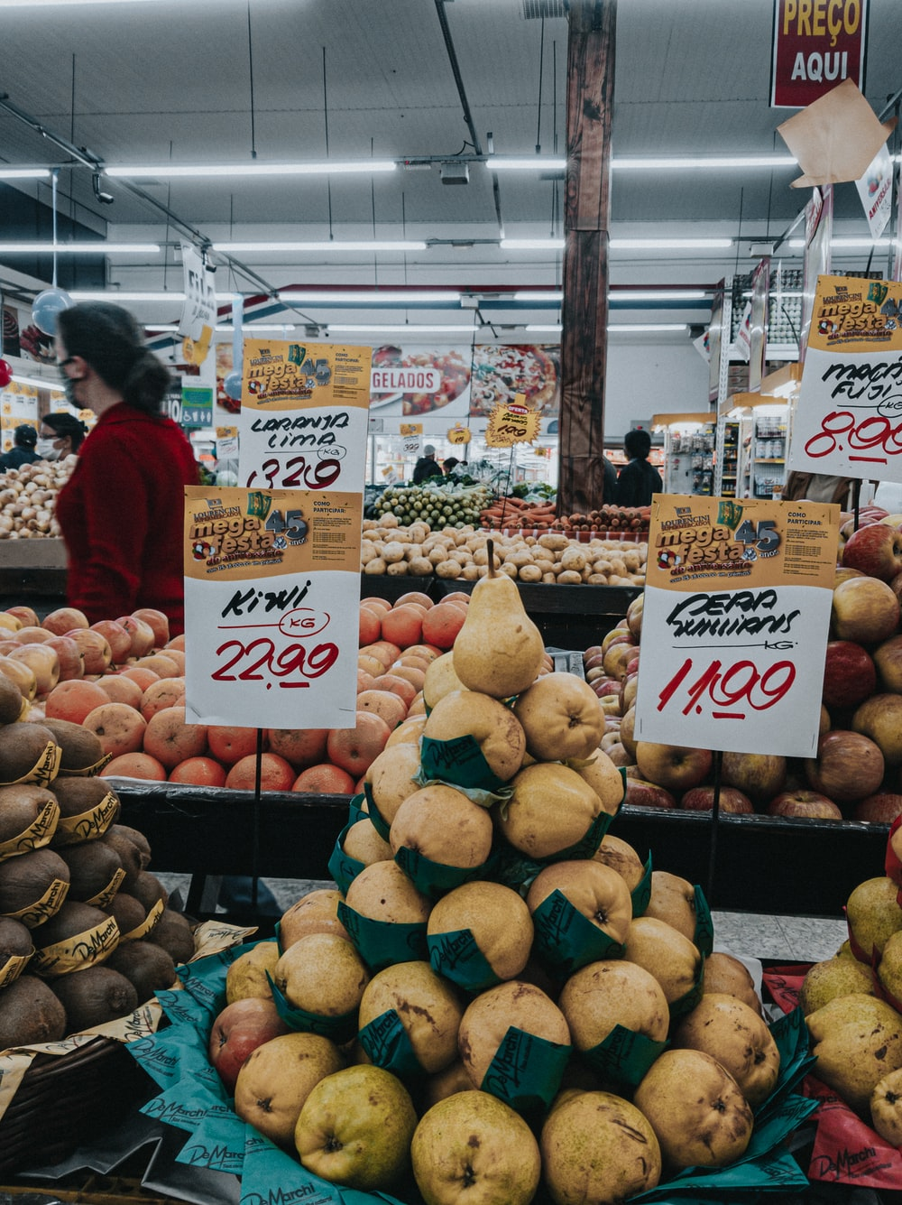 woman in red shirt standing near fruit stand