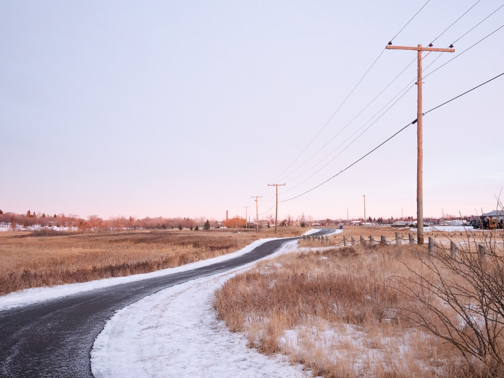 gray concrete road between brown grass field during daytime