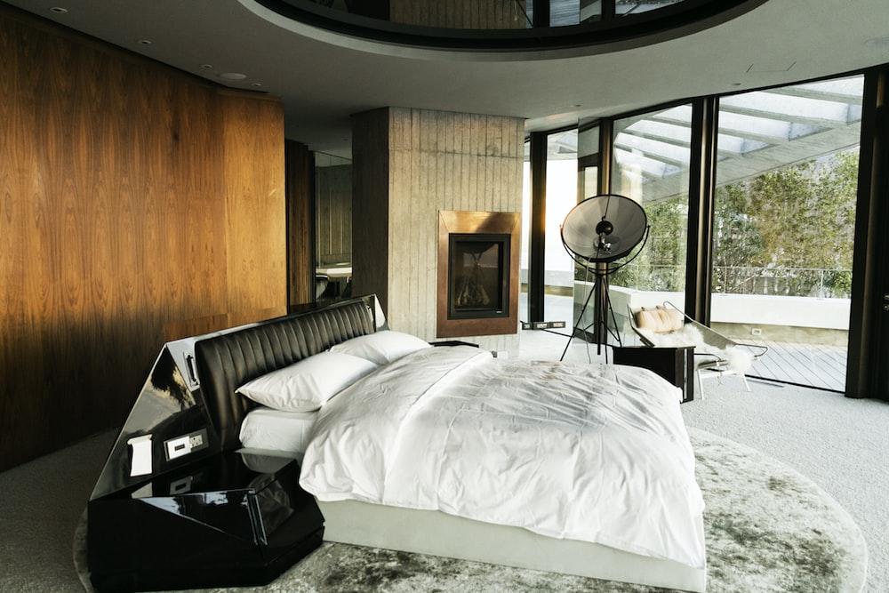 white bed linen near black table lamp