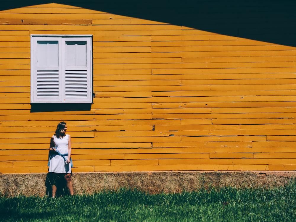 girl in white shirt and orange skirt standing on green grass field during daytime
