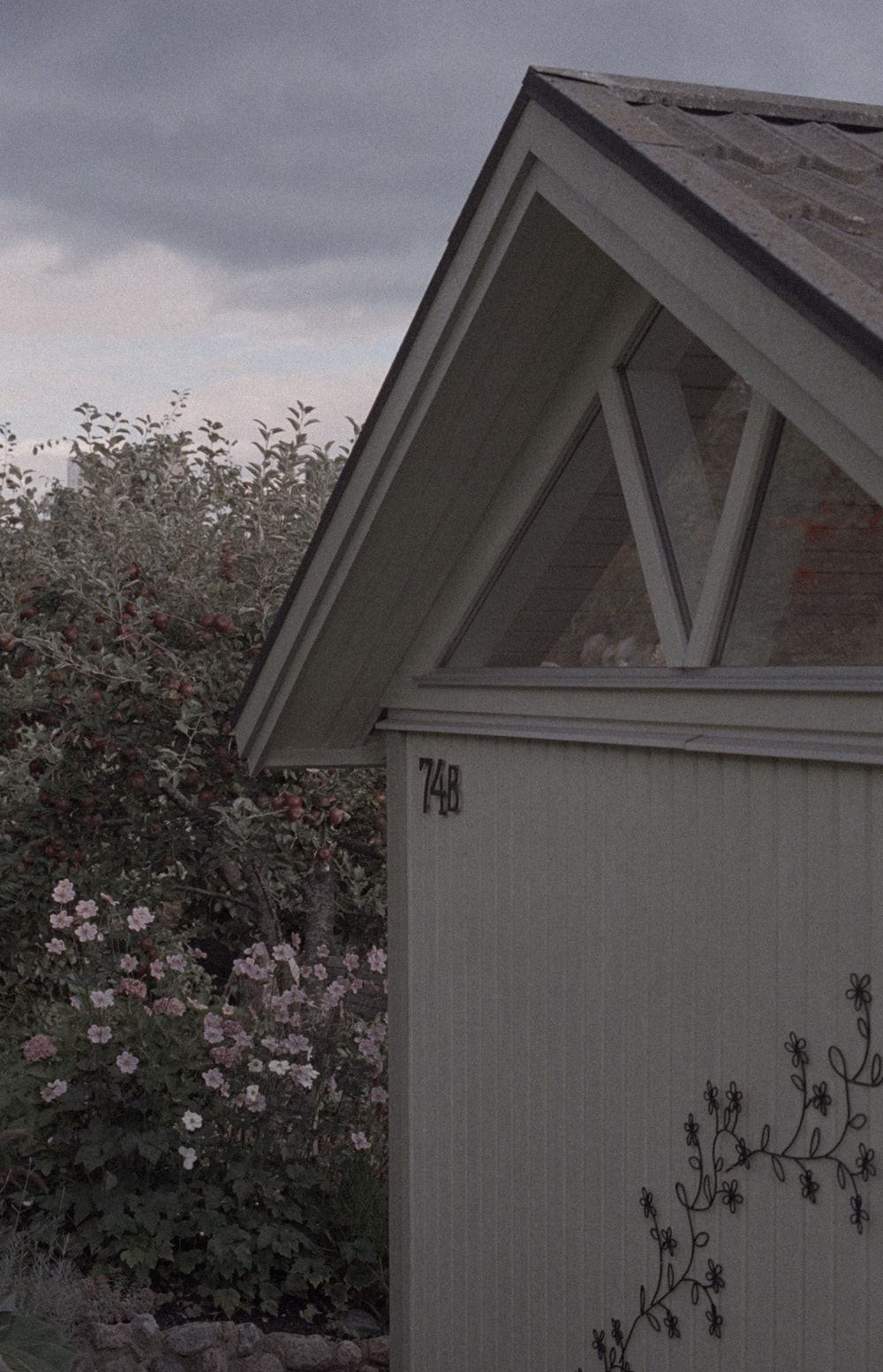 white wooden house with pink flowers