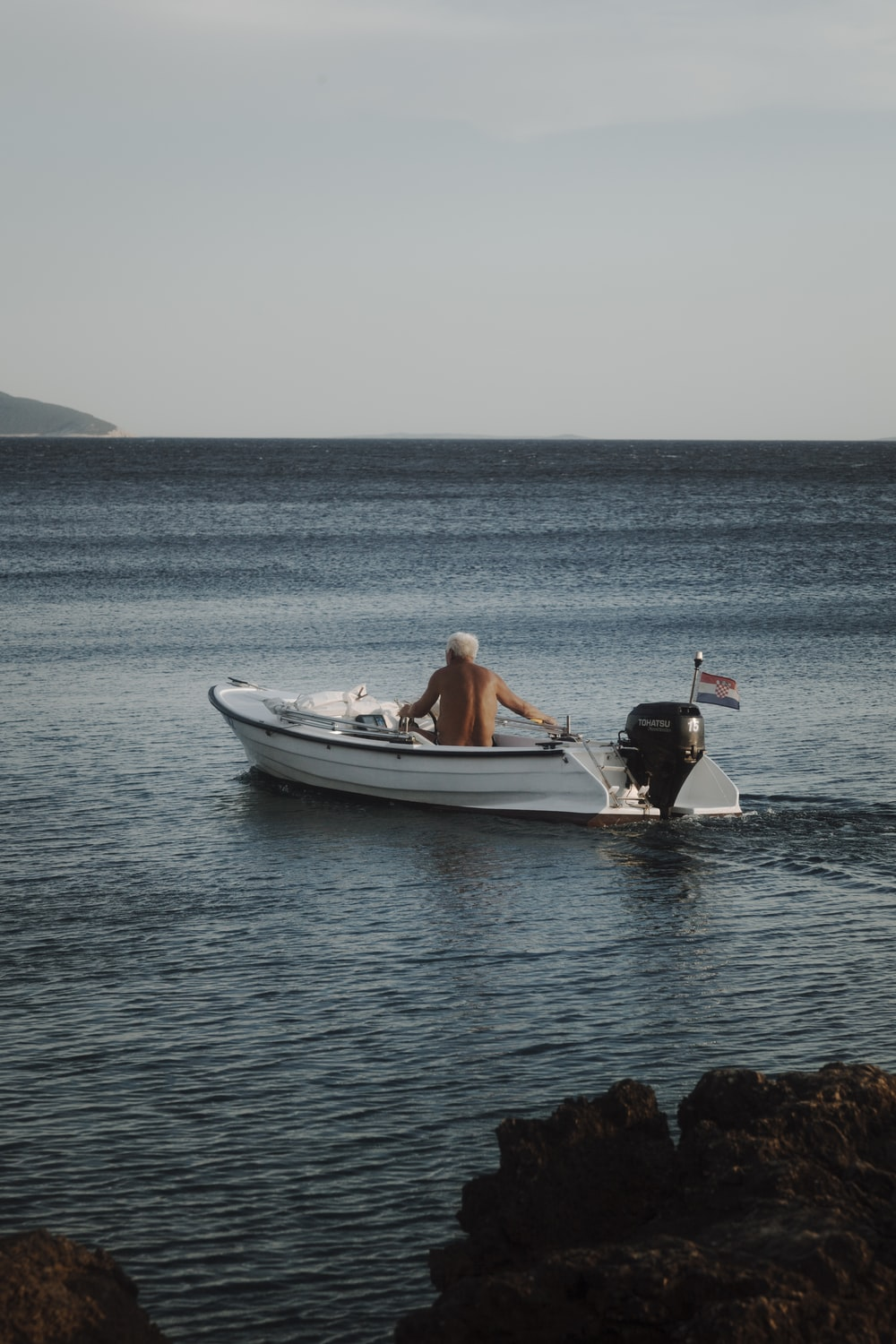 man in black shirt and black shorts sitting on white and blue boat on sea during