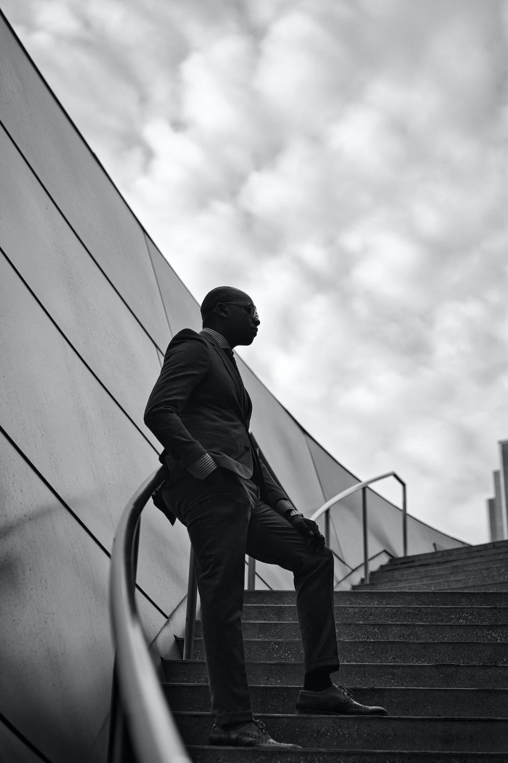 man in black jacket and black pants walking on stairs